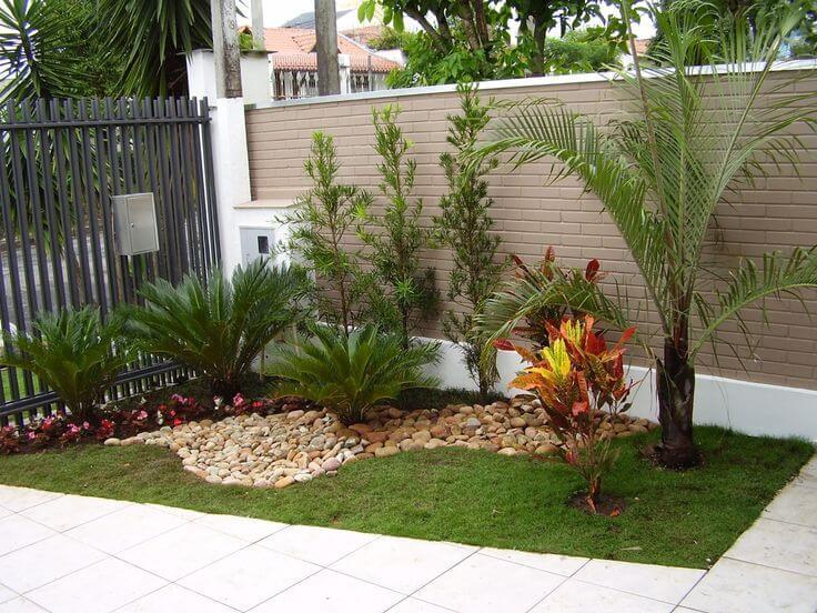 jardim de entrada no canto do muro com cascalhos