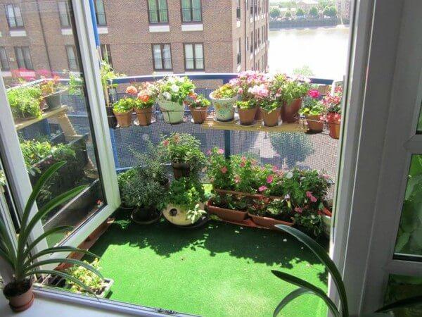 jardim pequeno com grama artificial na sacada