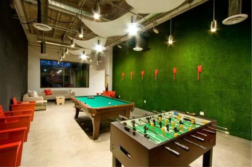 Sala de jogos de empresa com parede revestida em grama sintética
