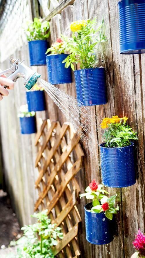 Moça regando horta vertical feita de latas metálicas