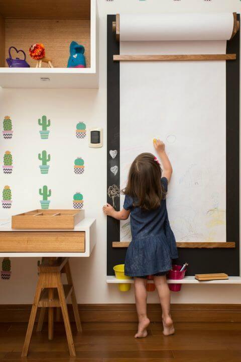 Menina desenhando em bobina de desenho