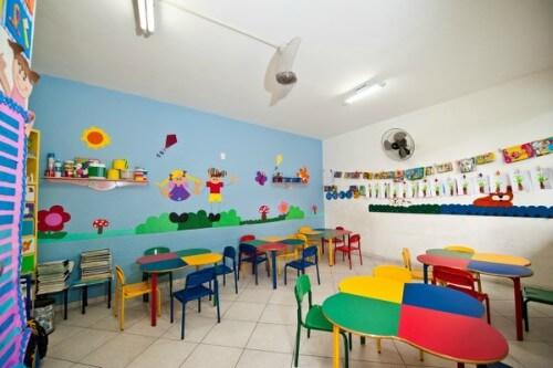 Sala de aula com paredes azul e mobiliário colorido