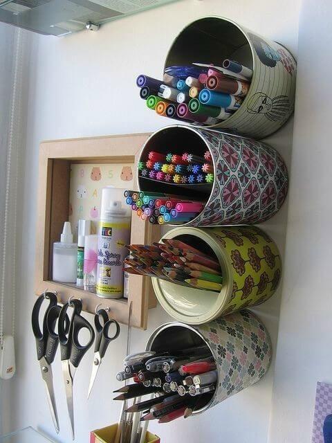 Latas metálicas sendo usadas para guardar lápis e canetas