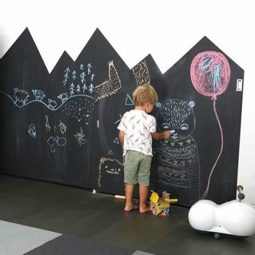 Criança desenhando em parede com tinta-lousa