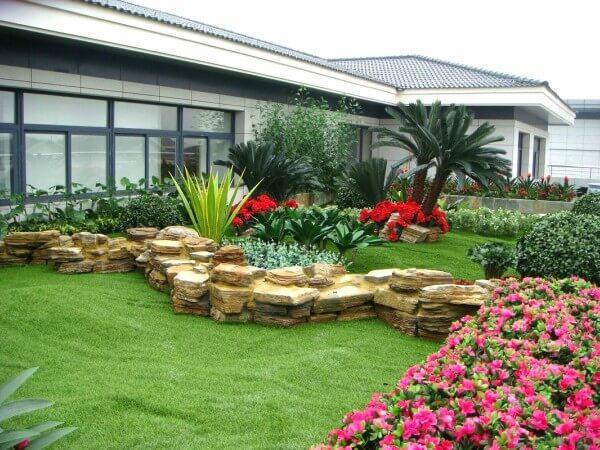 Na imagem, casa moderna com jardim de flores e grama sintética em sua frente.