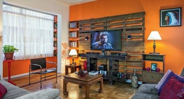 Imagem mostrando sala de casa com painel de TV feito de palete