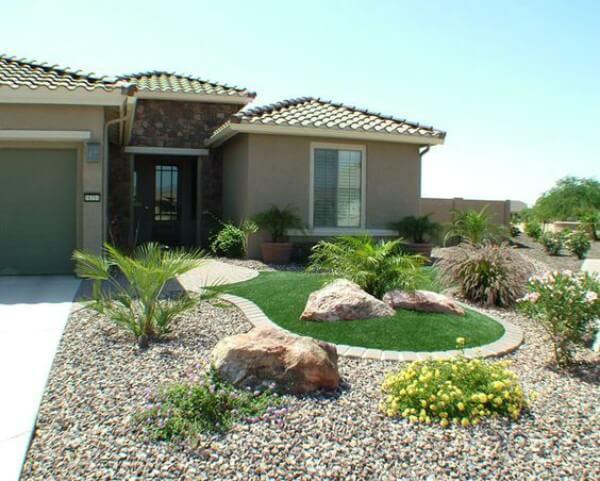 Casa moderna com paredes em tom pastel e quintal com grama sintético e pedras decorativas em sua frente