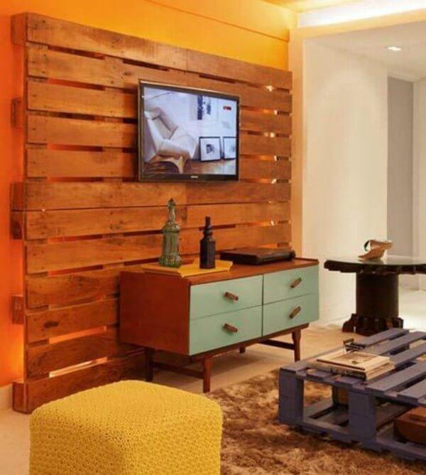 Sala de casa com painel de TV feito de palete