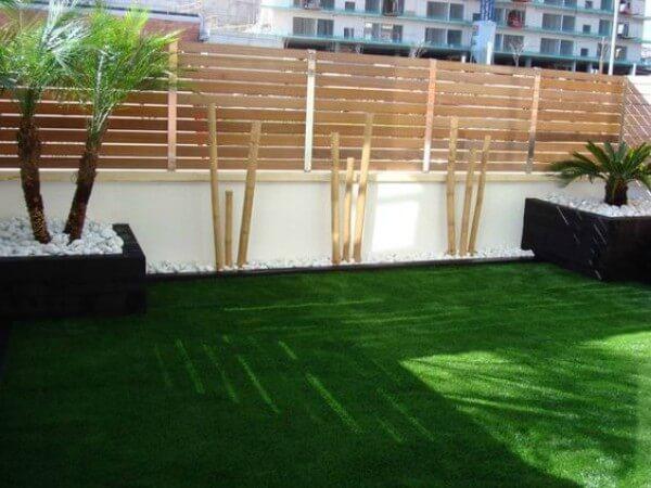 Imagem mostrando quintal decorado com grama sintética e paletes no muro