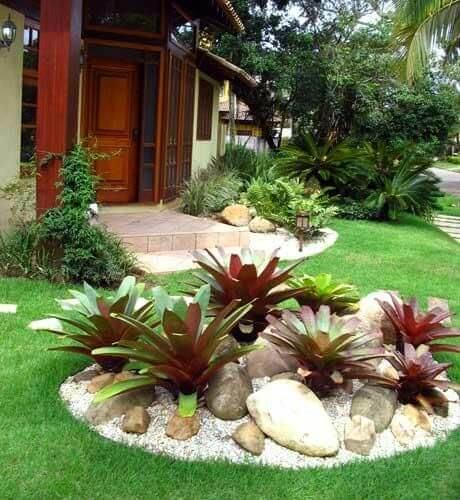 Imagem mostrando jardim de casa com grama sintética e folhagens