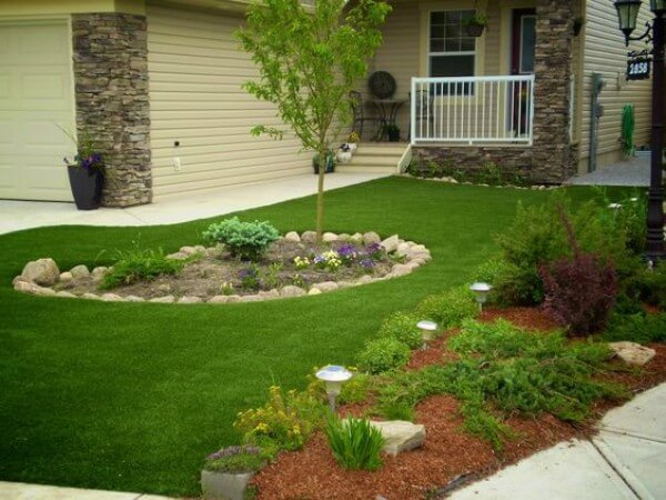 Imagem mostrando casa com jardim de grama sintética e pedras decorativas