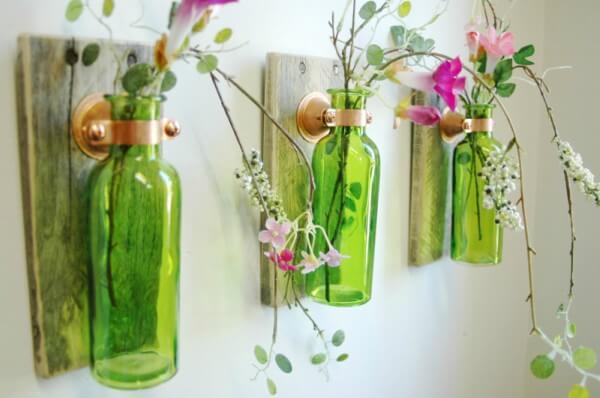 Garrafas verdes de vidro com plantas em ambiente fechado