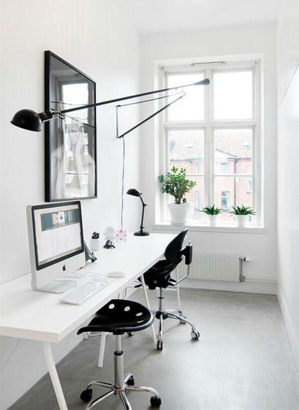 Escritório com paredes e móveis brancos e plantas bonsai