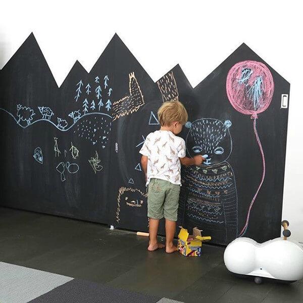 Criança desenhando em parede de lousa