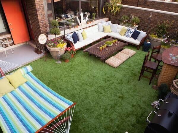 Jardim externo de casa com móveis e grama sintética