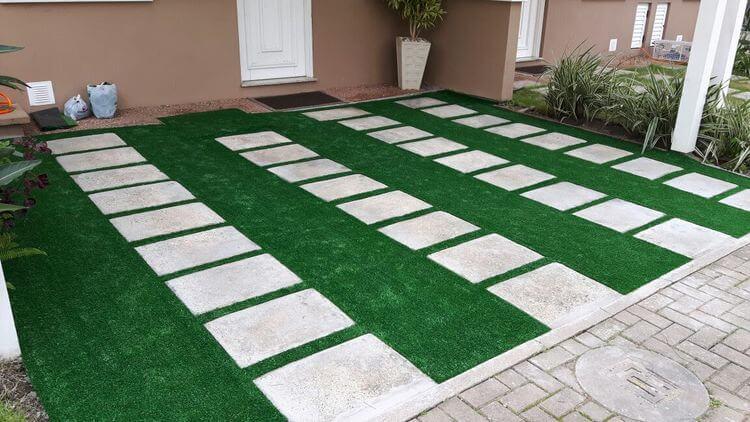 Garagem de casa com rejunte em grama sintética