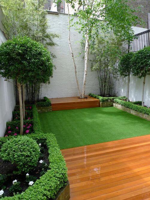 Quintal pequeno com piso de grama sintética e madeira