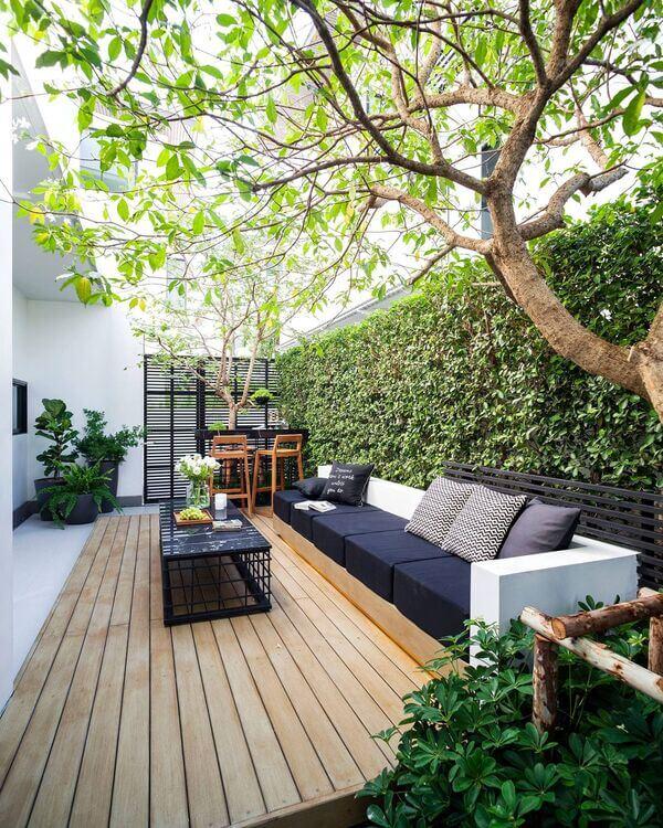 Quintal pequeno decorado com mesa, sofá e plantas