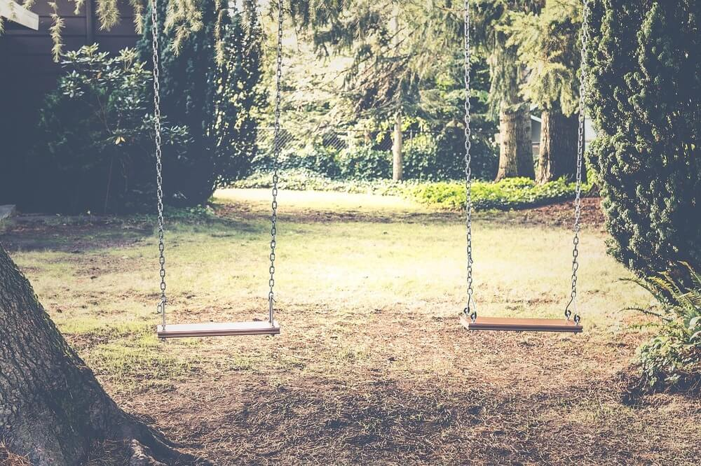Dois balanços em espaço arborizado