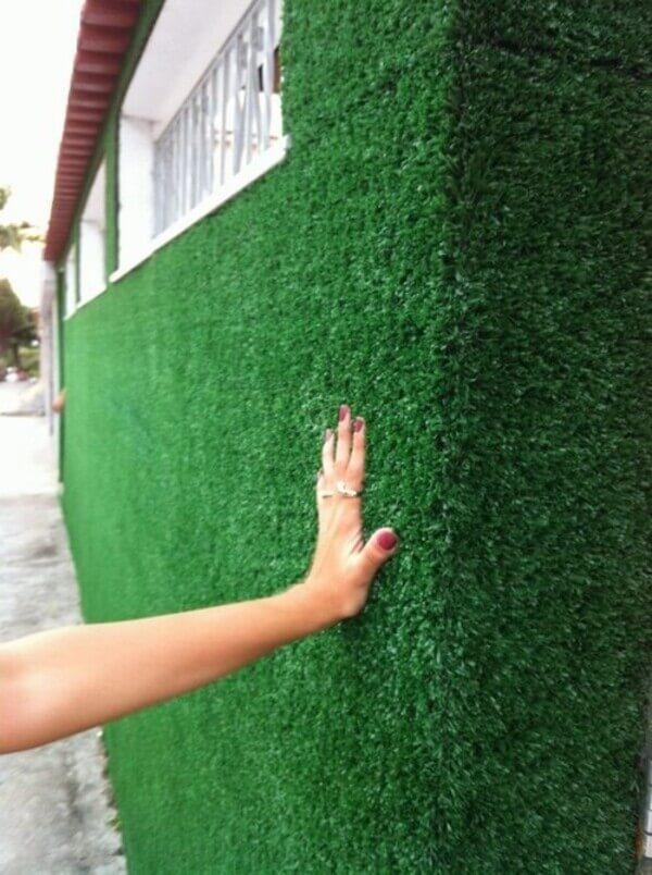 Mão tocando um muro de grama sintética