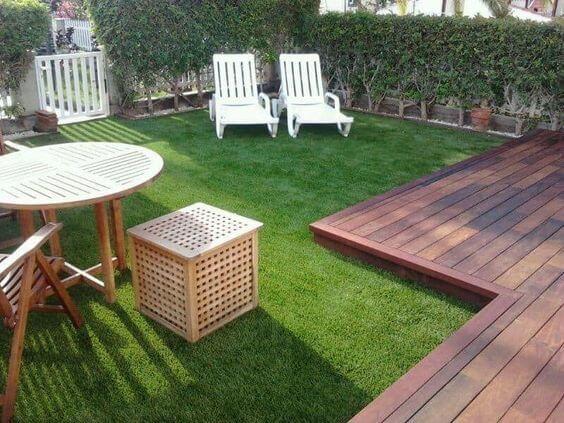 Varanda com piso de grama sintética e madeira