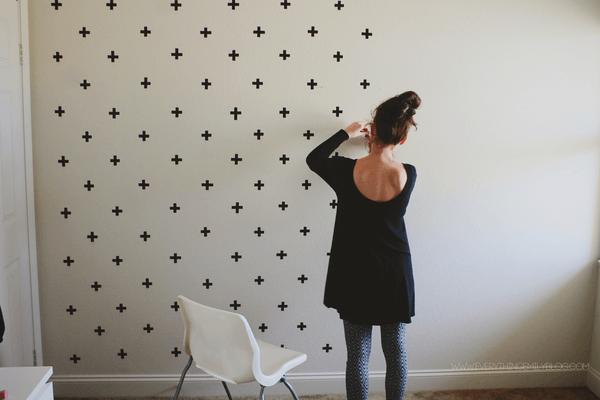 Mulher decorando parede com adesivos